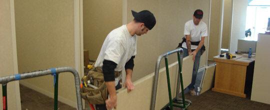 men moving office furniture parts